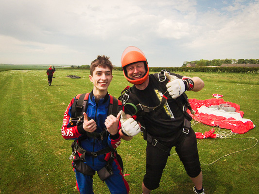 Tandem skydiver and instructor after landing